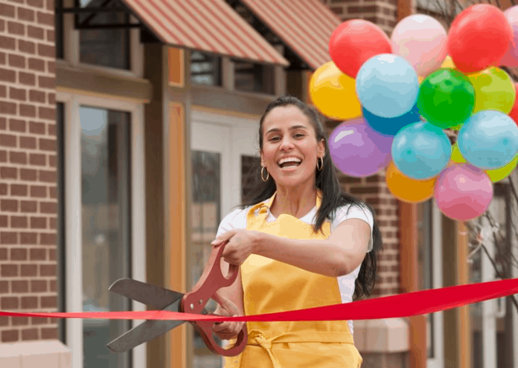 Image of a woman cutting a ribbon at her new store opening!
