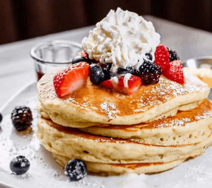Image of triple layer pancakes with berries and whipped cream