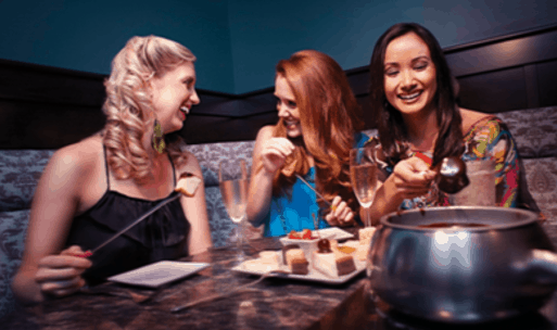 Image of 3 happy women dining at the Melting Pot Fondue