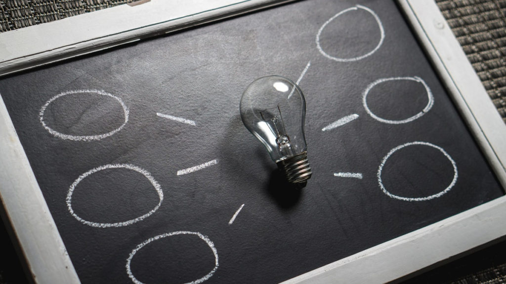 Marketing Content - Black and white chalkboard with light bulb and idea bubbles surrounding it.