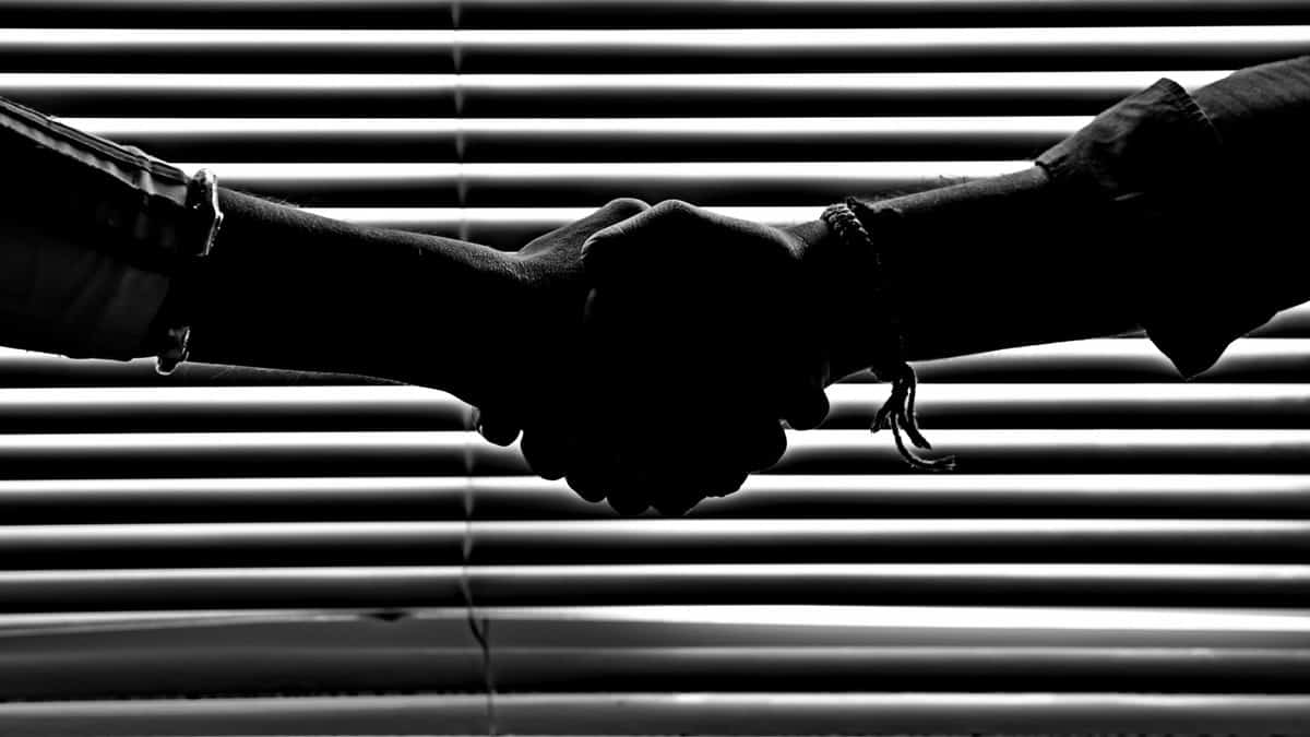 monochrome-photography-of-people-shaking-hands-814544.jpg